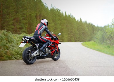 KRASNOYARSK, RUSSIA - May 29, 2018: Beautiful motorcyclist in full gear and helmet on a red and black Honda 2005 CBR 600 RR (PC37).