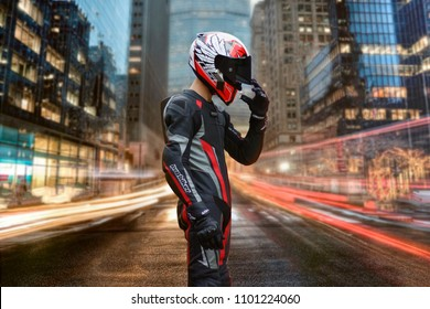 KRASNOYARSK, RUSSIA - MAY 30, 2018: A motorcyclist in full gear and helmet stands in the middle of the street. Night city