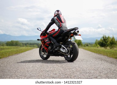 KRASNOYARSK, RUSSIA - May 31, 2019: Beautiful motorcyclist in full gear and helmet on a red and black Honda 2005 CBR 600 RR (PC37).