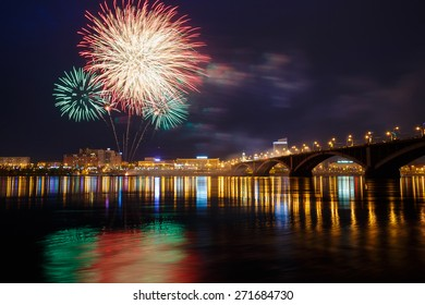 """Krasnoyarsk, Russia - May 9, 2014: Fireworks explode on the sky during celebrations of the """"Victory Day or or 9 May"""" that marks the capitulation of Nazi Germany to the Soviet Union in the part of the Second World War pictured on the street of Krasnoyarsk"""