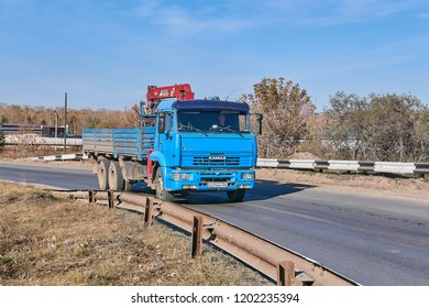 Krasnoyarsk, Russia - October 13, 2018:  KamAZ 65115 with the manipulator car moves on an outcome on Northern the Highway. Front right view.
