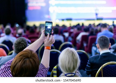 Krasnoyarsk, Russia, October 2019: People with mobile phone in the conference hall.