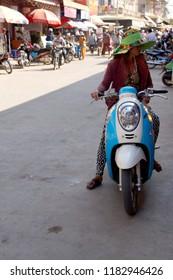 KRATIE, CAMBODIA - FEB 10, 2015 - Motorbike traffic at the local market in  Kratie, Cambodia