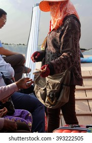 KRATIE, CAMBODIA - FEB 9, 2015 -Woman collects ferry fee from passengers, Kratie Province, Cambodia