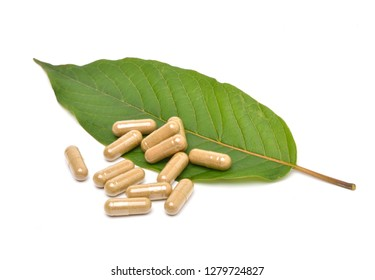 Kratom (Mitragyna speciosa) capsules with green leaf isolated on white background.