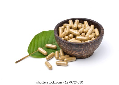 Kratom (Mitragyna speciosa) capsules in wooden bowl with green leaf isolated on white background.