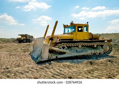 Kremenchug, Ukraine - 27 June 2008. Yellow bulldozer leveled ground brought dump trucks.