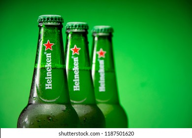 KREMENCHUG, UKRAINE - SEPTEMBER 24, 2018. Heineken Lager Beer with drops on green background. Dutch brewing company Heineken
