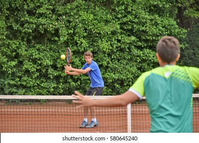 KREMS, AUSTRIA - JUNE 16, 2016: Male teenage tennis player hitting a forehand with his opponent in front