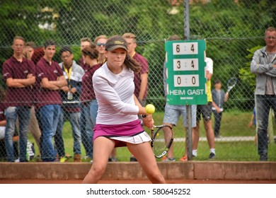 KREMS, AUSTRIA - JUNE 16, 2016: Female teenage tennis player hitting a backhand with audience in background