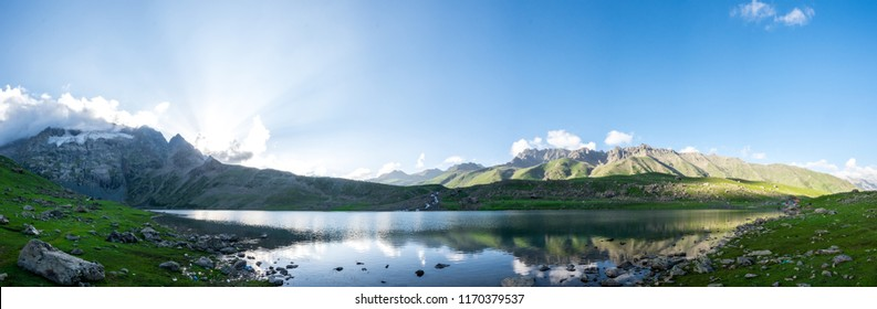 Krishnasar and Vishnusar lakes on the Kashmir great lakes trek in Sonamarg, India. Rocky terrain and turquoise lake/tarn with snow mountains and glacier. Most serene trek in the Himalayas. Panorama.