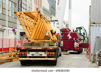 Kristiansand, Norway - August 1, 2017: Documentary of everyday life in the city. Construction worker securing crane parts on truck for transport. Mobile crane on street in background.