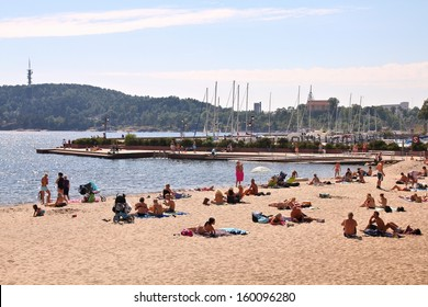 KRISTIANSAND, NORWAY - AUGUST 9: People relax on the beach on August 9, 2010 in Kristiansand, Norway. Kristiansand is the 5th largest municipality in Norway (90 thousand people).