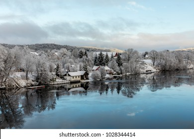 Kristiansand, Norway - January 17, 2018: Scenic view of the Tovdal River at Tveit, with houses by the riverside. Winter time, snow in the trees. Ice floating in the water, reflections of the sky.