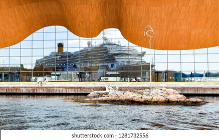 Kristiansand, Norway - July 19, 2017: The cruise ship Costa Favolosa of Costa Cruises is reflected in the glass facade of the Kilden Performing Arts Center.