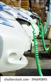 Kristianstad, Sweden - March 20, 2016: The charging of some white Nissan electrical cars. Green coiled cables are attached to the front of the cars. These are C4 Energi carpool rentals.