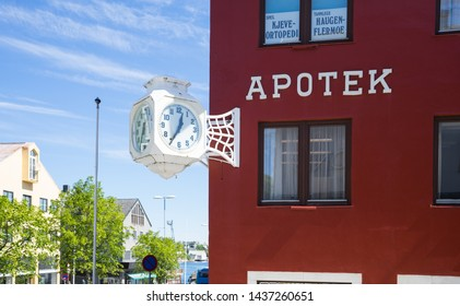 Kristiansund / Norway - June 15 2019: Building with label Pharmacy (Apotek). Bordeaux red wall. Designed white cube shaped street clock attached to the wall.