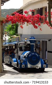 KRITSA, CRETE – MAY 13, 2017: A sightseeing tourist train transports visitors through the blooming, flower-filled village of Kritsa, Crete, Greece on a sunny day.