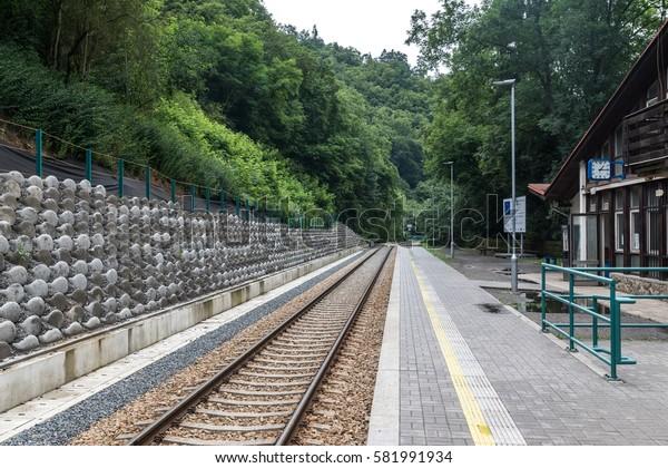 KRIVOKLAT, CZECH REPUBIC - 31 july 2016: Railway station and passengers platform Krivoklat. Railway platform in the Czech Republic after the reconstruction: modern tile, new rails and sleepers