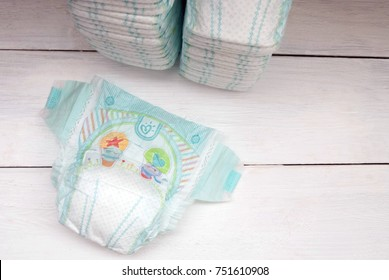 Krivoy Rog, Ukraine, 11/05/2017. Set of disposable diapers on a white wooden background