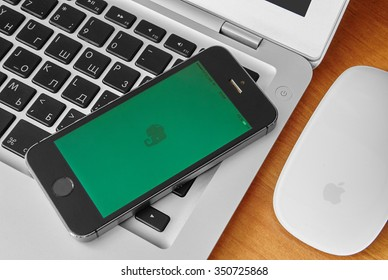 KRIVOY ROG, UKRAINE - december 12, 2015: iPhone 5s with mobile application for Evernote on the screen. Silver macbook air with apple magic mouse, Wooden background.