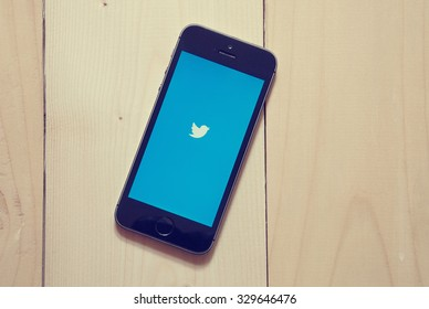 """KRIVOY ROG, UKRAINE - OCTOBER 20, 2015: iPhone 5s with Twitter app on wooden background. Twitter is an online social networking and microblogging service that enables users to send and read """"tweets"""""""