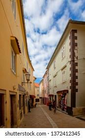 KRK Croatia April 7 2019: People walking in the narrow street with medieval stones houses in town of KRK Croatia.