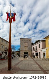 KRK Croatia April 7 2019: An unidentified lady posing  in the town square with medieval stones houses in town of KRK Croatia.
