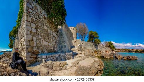 KRK Croatia April 9 2019: Visitor enjoying the sun at the Fortification of Krk town, capital of Krk island.