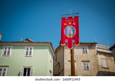 KRK, CROATIA - AUGUST 30, 2019: Coat of Arms in the Center Square of town Krk. Buildings in the background. Krk town is a famous touristic destination on Krk island, Croatia