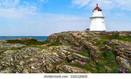 The Krogsta lighthouse in rocky coastal landscape on a sunny morning. An empty bench is visible beside the lighthouse.