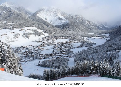 Kronplatz, Italy, 2018: Ski slope and village in a valley, high peaks in the background in a beautiful winter day