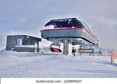 Kronplatz, Italy, 2018: Upper station of the modern heated cableway with a bubble for 6 people, photo of chairlift made in beautiful snowy winter day