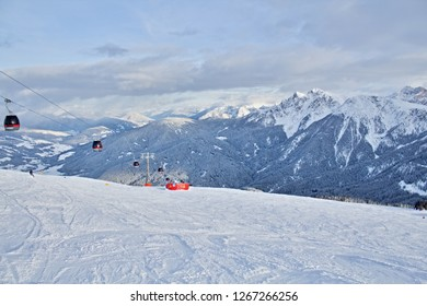 Kronplatz, Italy, 2018: Wide ski slopes and a cableway in the ski resort in Italian Dolomites, valley and peaks in the background, panoramic nature photo taken in beautiful sunny day