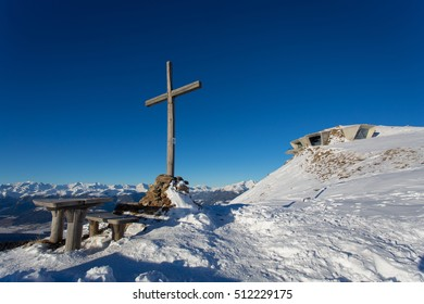 KRONPLATZ, ITALY - JANUARY 21, 2016: Memorial cross on the background of the Messner Mountain Museum. Museum is situated on the plateau of Kronplatz and was created by Zaha Hadid, Brunico, Italy.