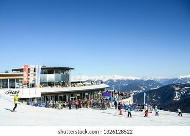 Kronplatz, South Tyrol, Italy - February 15, 2019: people enjoy skiing and sunbathing at Kronplatz Plan de Corones ski resort in the snowy Dolomites on a beautiful sunny day with clear blue sky