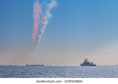KRONSHTADT, RUSSIA - JULY 28, 2018. Celebration of the Day of the Russian Navy. Russian cruiser Marshal Ustinov - Slava-class cruiser of the Russian Navy and Russian smoke flag in the sky