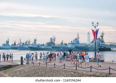 KRONSTADT, ST. PETERSBURG, RUSSIA — JULY 28, 2018: People on the pier on the background of naval ships before the Navy Day parade in Kronstadt town