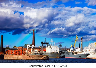 Kronstadt, a town and naval base on Kotlin Island, Baltic Sea, near St. Petersburg, Russia. Ships moored at the military seaport, old shipyard building and beautiful sky with clouds and rainbow