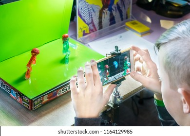 KROPIVNITSKIY, UKRAINE – 12 MAY, 2018: Stop motion animation process with Stikbot details and toy figures. Boy expose stop motion elements to create animations using smartphone