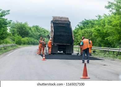 KROPIVNITSKIY, UKRAINE – 27 MAY, 2018: Road repair concept. Road construction equipment and Workers on highway. Tractors, trucks, roller on the road repair site. Fresh asphalt construction. Bad road