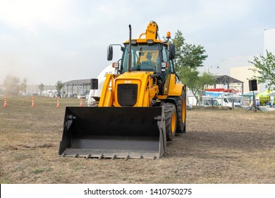 Kropivnitskiy, Ukraine April 20, 2019: The JCB bucket loader in motion at a demonstration site agro exhibition AgroExpo. Tractor rides on the field.