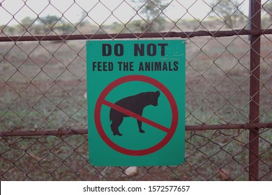 Kruger National Park, South Africa, June 2016,Warning sign on green with black hyena and red circle to warn against feeding wild animals in park,