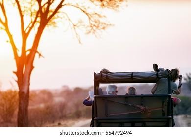 KRUGER NATIONAL PARK, SOUTH AFRICA - November 6, 2016. Tourists taking photos on a safari drive through Kruger National Park at sunset