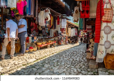 KRUJA, ALBANIA - AUGUST 10, 2018: Perspective view of people in a medina street market with souvenirs, craft items and small shops in Kruja Albania August 10, 2018.