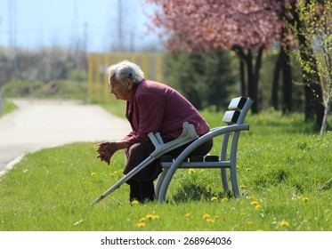 KRUSEVAC, SERBIA - APRIL 13 2015 Mature woman with crutches next to her, resting on a bench in a park called Bagdala relaxing and contemplating in the spring sun