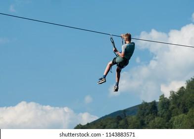 Kruth - France - 27 July 2018 - young boy descend on a zipline in mountain landscape background