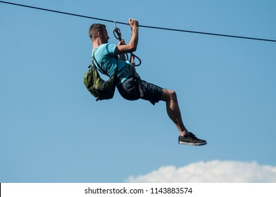 Kruth - France - 27 July 2018 - man with backpack  descend on a zipline in mountain landscape background