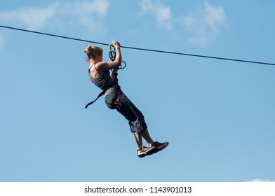Kruth - France - 27 July 2018 -  Woman descend on a zipline in mountain landscape background
