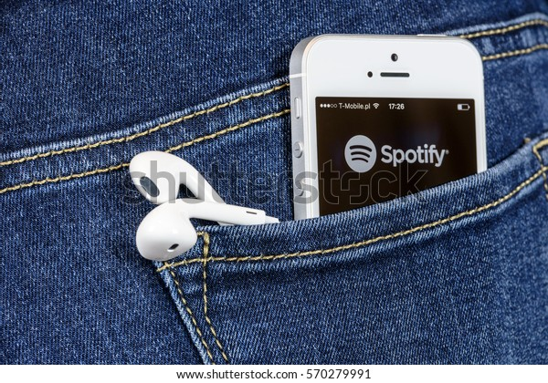 Krynica, Poland - February 02, 2017: Spotify app on iPhone SE screen in blue jeans pocket. Spotify is one of the most popular music service app on the world.